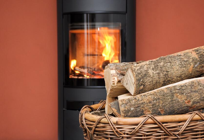 brennender Kaminofen mit Holzscheiten und Edelstahlschornstein