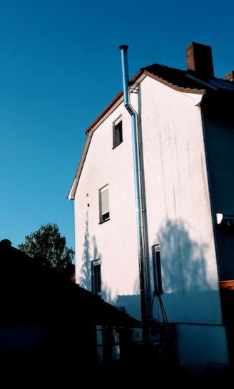 Edelstahlschornstein an der Außenwand eines Hauses